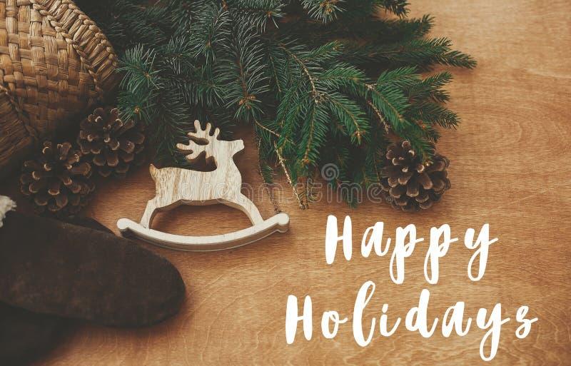Happy Holidays-Textschild auf Rentierspielzeug, Handschuhen, Korb mit Tannenfäden und Kegel auf rustikalem HolzHintergrund Flachl stockbild