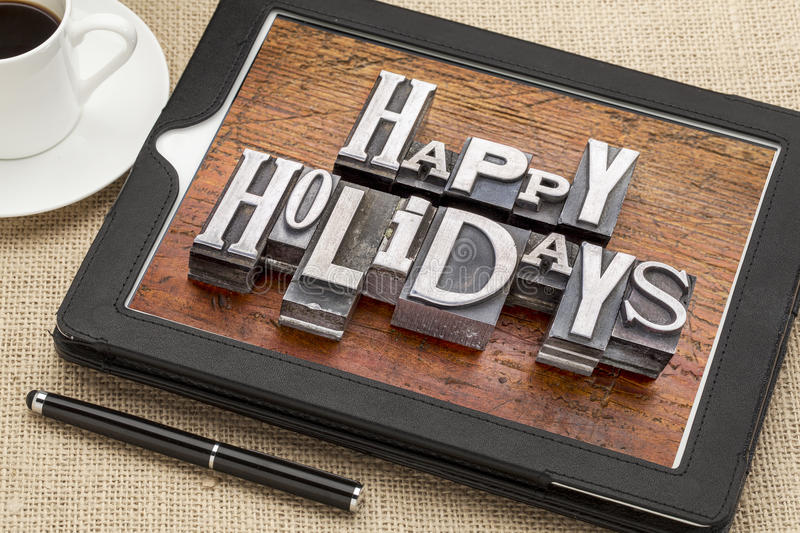 Happy Holidays typography. Happy Holidays greetings in vintage metal type printing blocks on a digital tablet with a cup of coffee royalty free stock image
