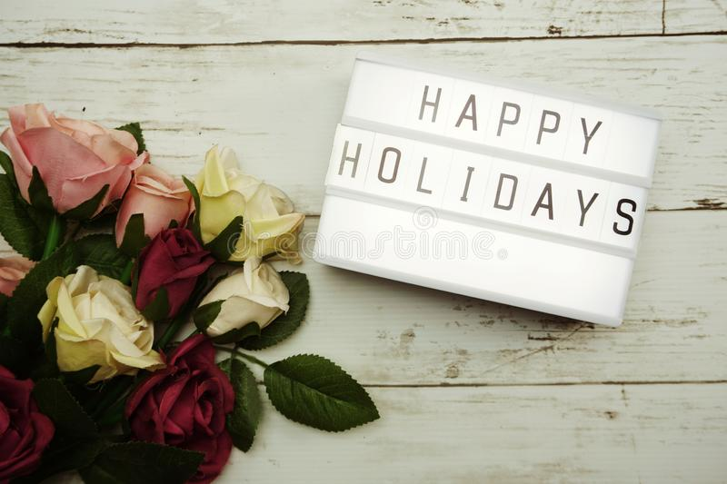 Happy Holidays Word on Light box with roses flower bouquet on wooden background stock photo