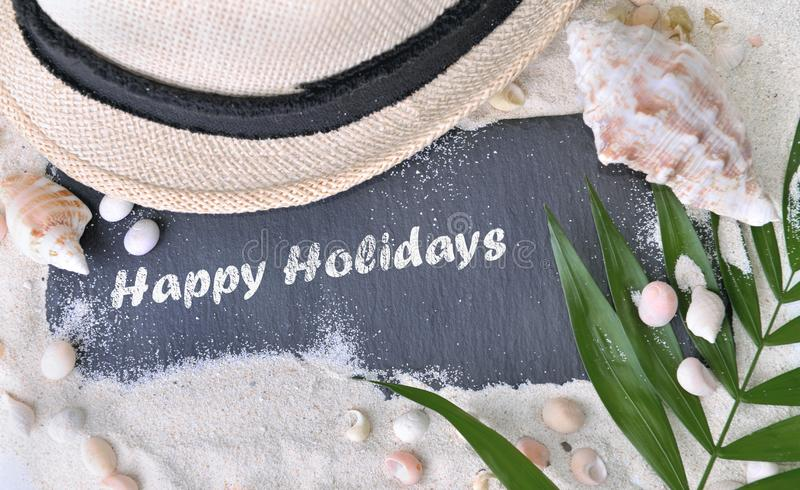 Happy holidays written on a slate in the sand stock image