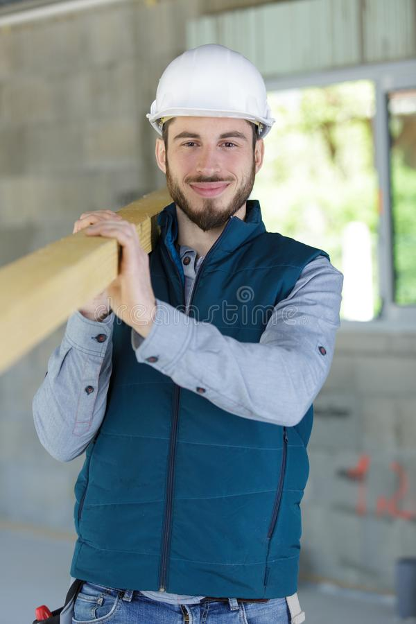 Happy home builder carrying wood. Builder stock photography