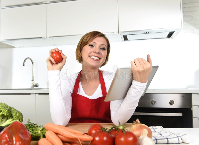 Happy home cook woman in apron at kitchen using digital tablet as cookbook. Young happy home cook woman in red apron at domestic kitchen using digital tablet as stock photos