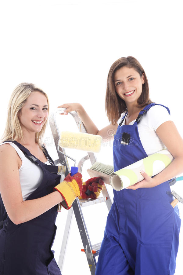 Happy home decor team. Of two smiling female friends in overalls about to embark on a wallpapering project stock photos