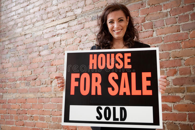 Happy homeowner sold her house. For sale by owner concept royalty free stock photos