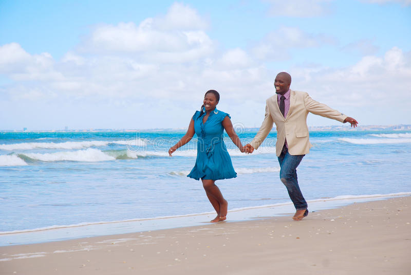 Happy honeymoon couple. An African American black couple with happy smiling facial expression running together hand in hand on the beach on the day of honeymoon