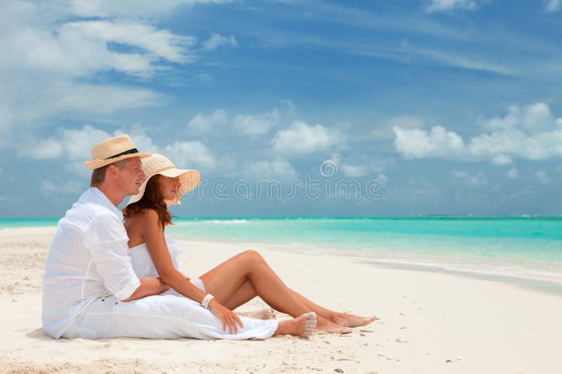 Happy honeymoon vacation at summer. Couple relax on the white sand of beach. Happy sea lifestyle. Young family, man and woman rest royalty free stock photo