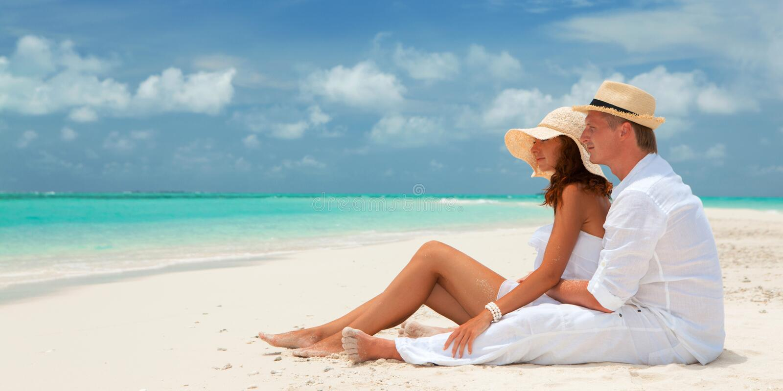 Happy honeymoon vacation at summer. Couple relax on the white sand of beach. Happy sea lifestyle. Young family, man and woman rest stock image
