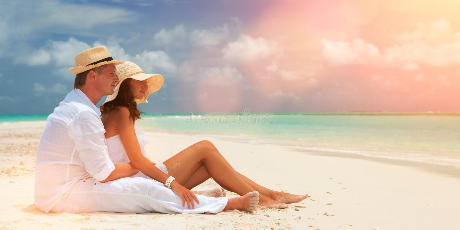 Happy honeymoon vacation at summer. Couple relax on the white sand of beach. Happy sea lifestyle. Young family, man and woman rest stock images