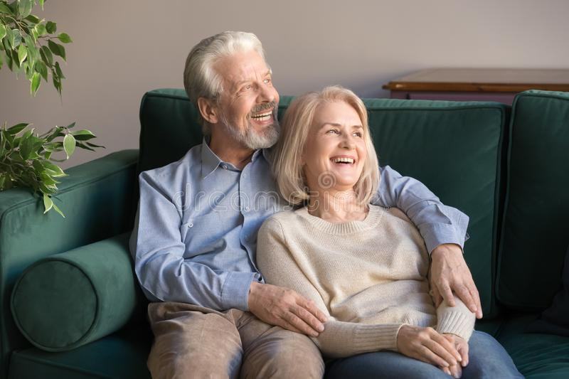 Happy hopeful old couple embracing resting on couch looking away stock images