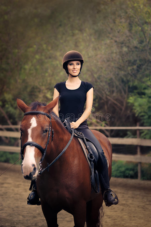 Happy Horsewoman Ridding in a Manege. Cute girl wearing a safety helmet practicing riding stock photo