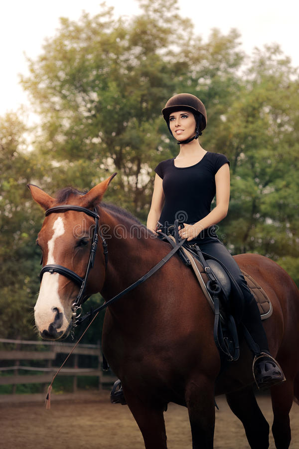 Happy Horsewoman Ridding in a Manege. Cute girl wearing a safety helmet practicing riding stock photography