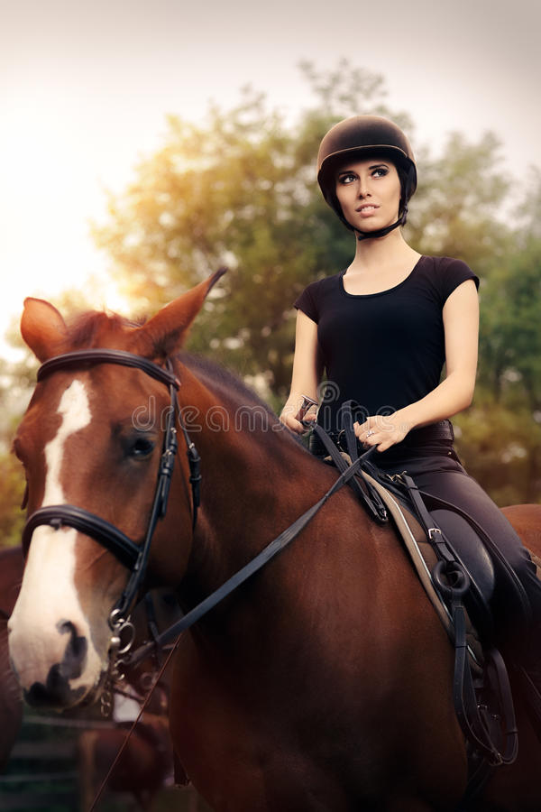 Happy Horsewoman Ridding in a Manege. Cute girl wearing a safety helmet practicing riding stock images