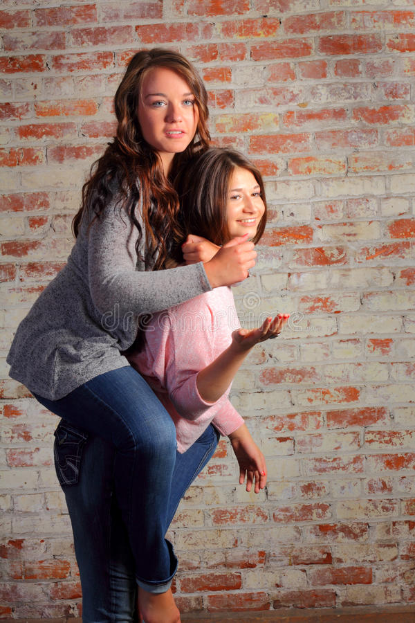 Happy Horsing Around. Two pretty brunette teenage girls having fun horsing around playing piggyback in front of a brick wall stock photos