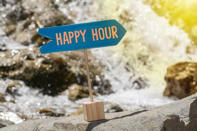 Happy hour board on rock. Happy hour wooden sign board arrow on rock , river and sun shine background royalty free stock images