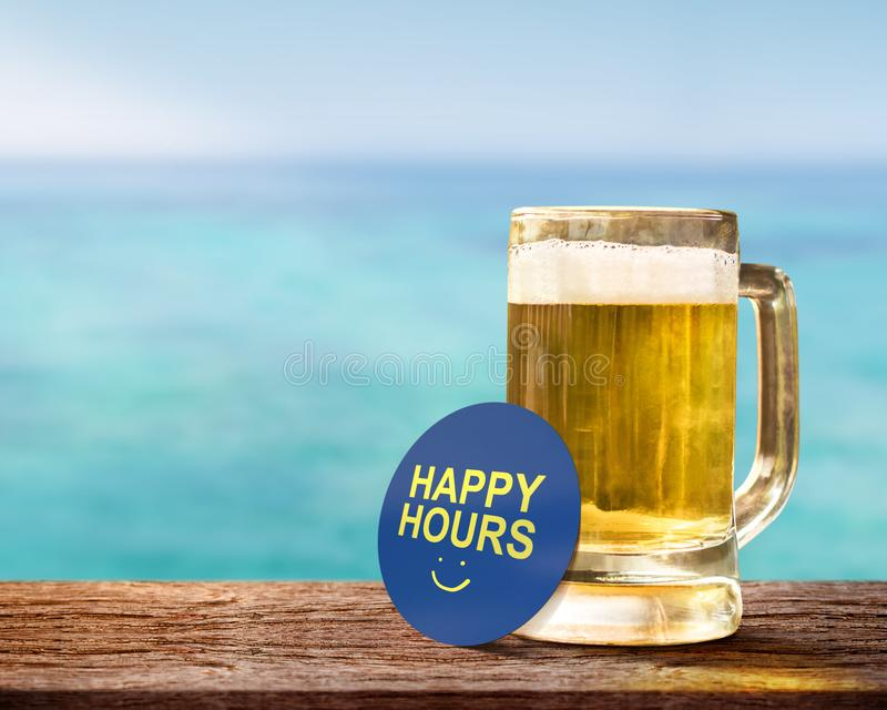 Happy Hour Concept for Bar, Cafe or Hotel Resort to Promote a Sp. Ecial Offer to Customer. Glass of Beer on Wooden Table with Smiley Face and Text on Note stock photography
