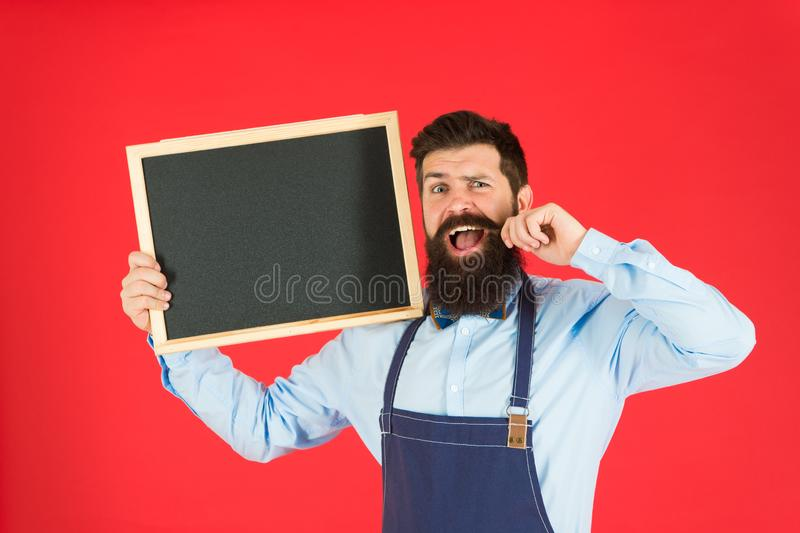 Happy hours bar. Man bearded bartender or cook in apron hold blank chalkboard. Price list concept. Hipster bartender. Show blackboard copy space. Hipster stock photos