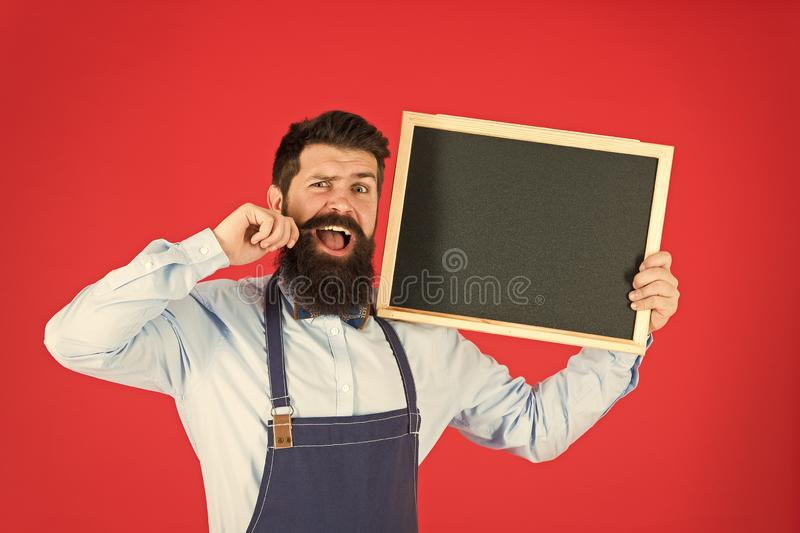 Happy hours bar. Man bearded bartender or cook in apron hold blank chalkboard. Price list concept. Hipster bartender. Show blackboard copy space. Hipster stock image
