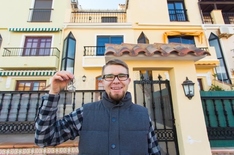 Happy house owner. Smiling young man holding keys and looking at camera while standing against new home background royalty free stock photos