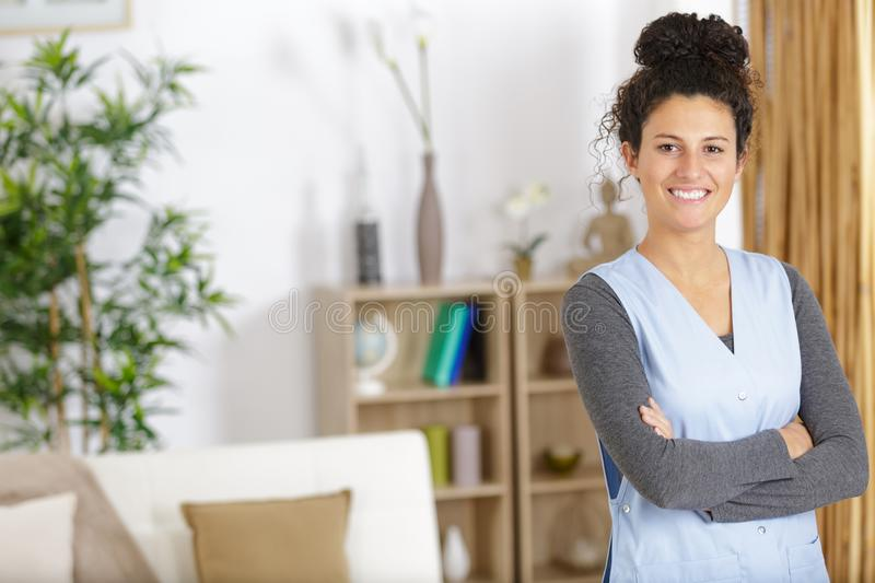Happy housekeeper looking at camera. Woman stock photo