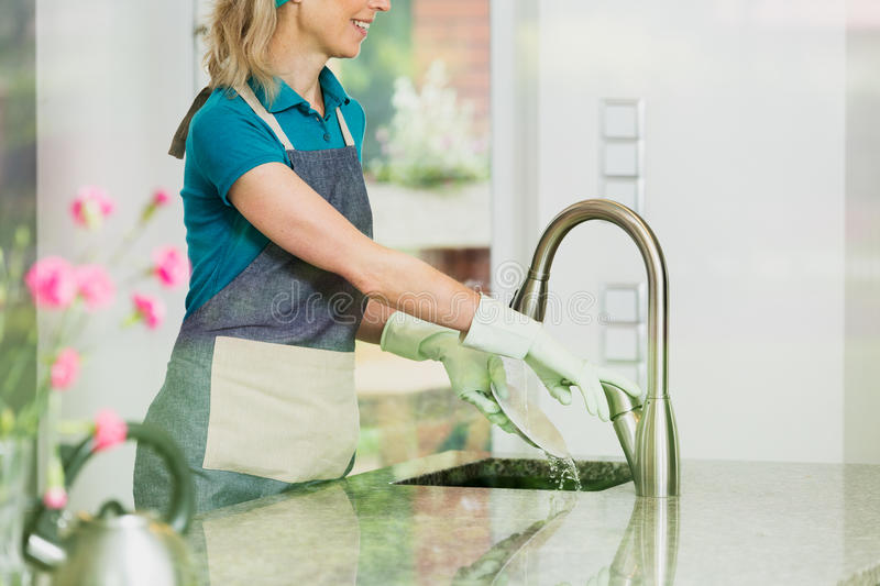 Happy housekeeper washes a plate. In kitchen sink with gloves on hands royalty free stock image
