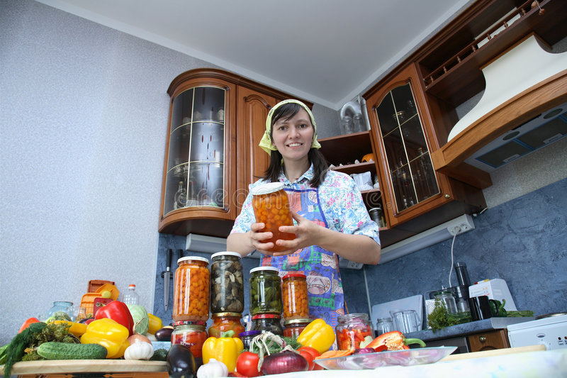 Happy housewife. Brags of canned food of own preparation royalty free stock photos