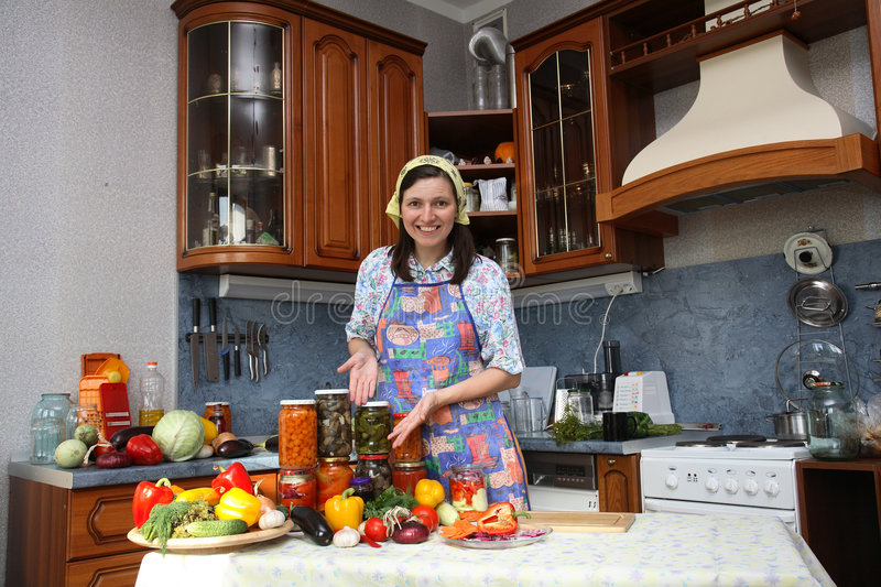 Happy housewife. Brags of canned food of own preparation royalty free stock image