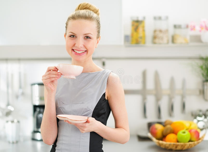 Happy housewife drinking tea in modern kitchen stock photo for Modern housewife