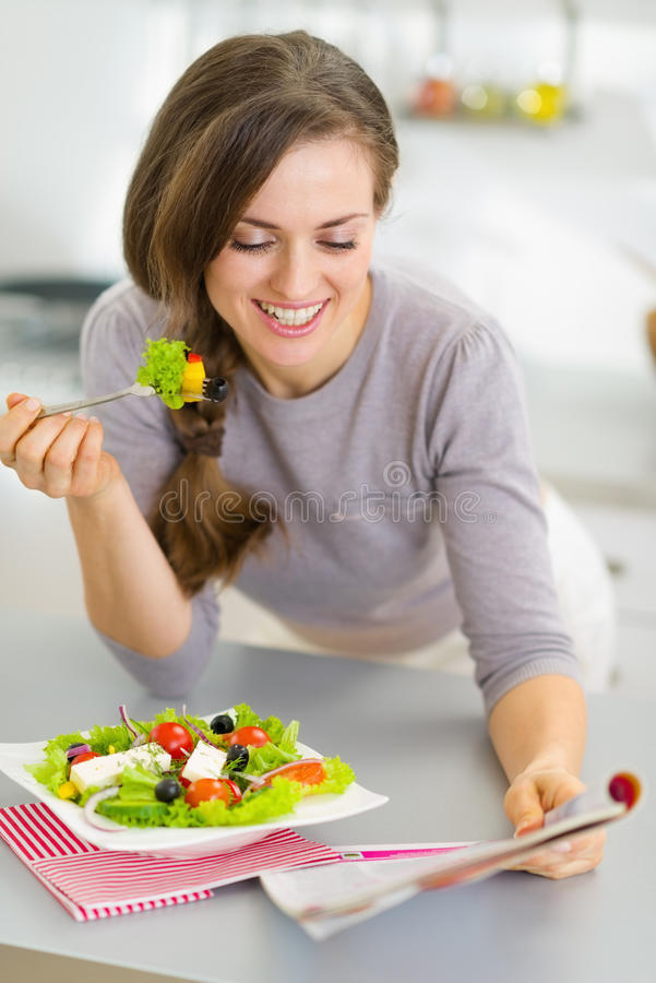 Happy housewife eating fresh salad and reading magazine royalty free stock images
