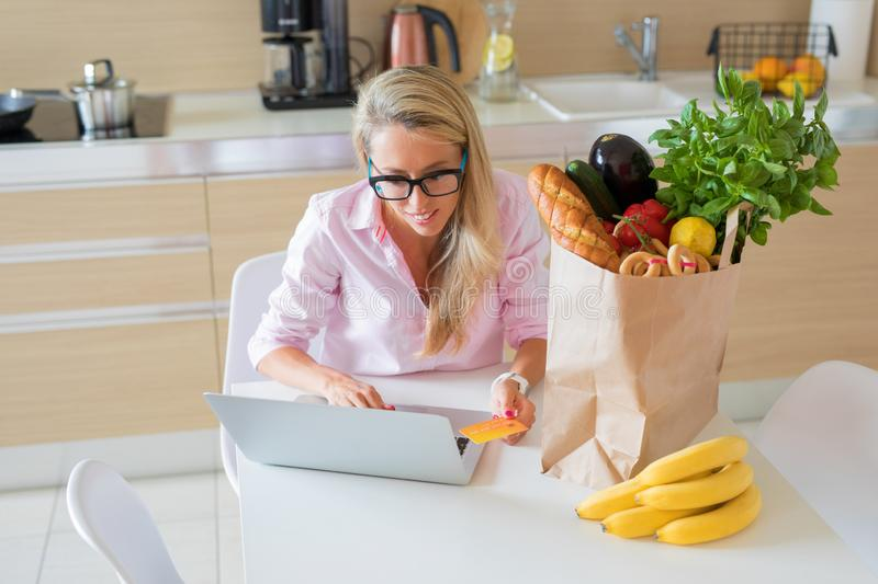 Housewife ordering groceries online and paying with credit card. Happy housewife ordering groceries online and paying with credit card royalty free stock photo