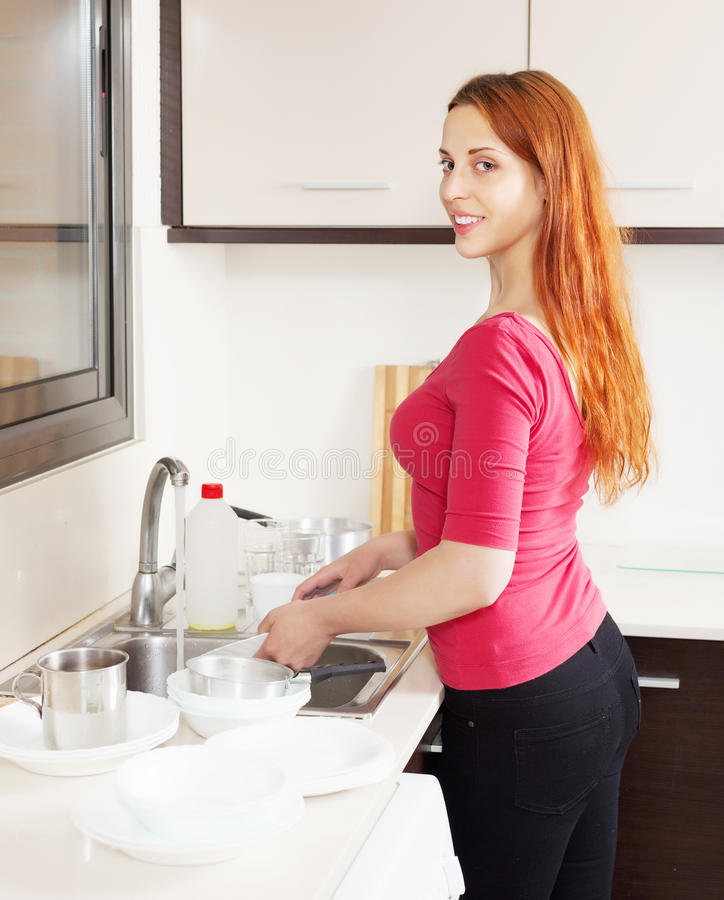 Happy housewife in red washing kitchenware royalty free stock photo