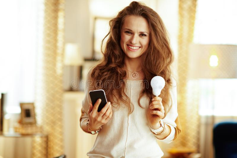 Happy housewife with smartphone and smart lamp in modern house. Portrait of happy fit housewife with long brunette hair with smartphone and smart lamp in the royalty free stock photo