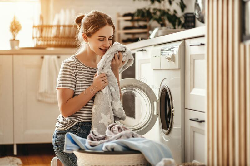 Happy housewife woman in laundry room with washing machine royalty free stock photo