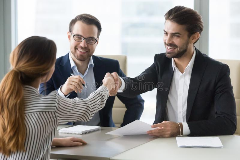 Happy hr manager shaking hand female job seeker. stock photo
