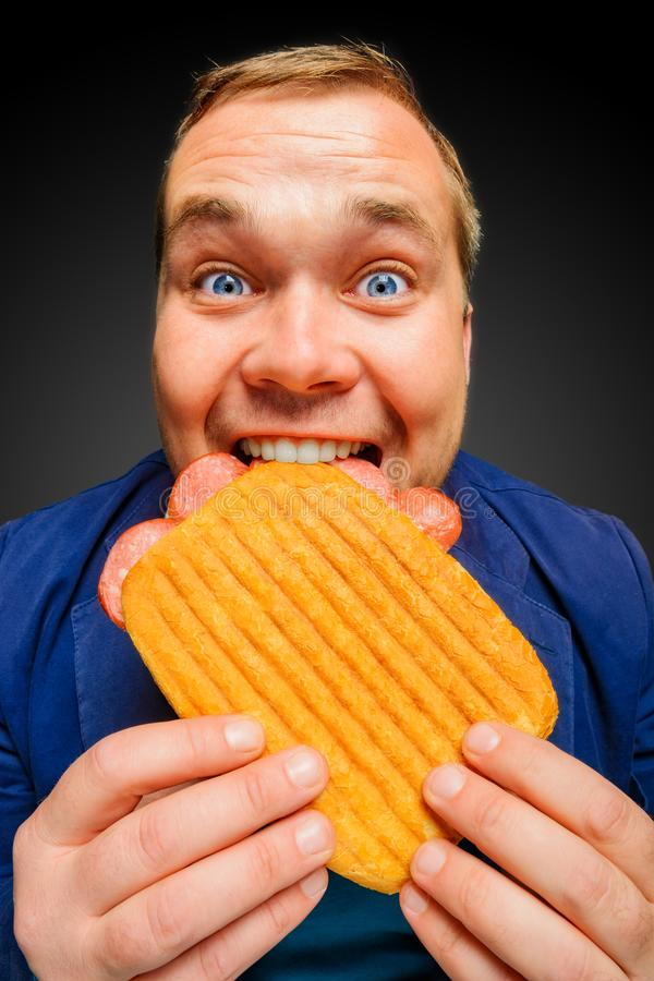 Happy hungry man eating the tasty panini sandwich stock image