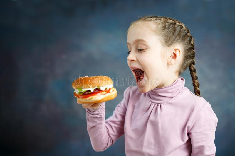 Happy hungry moments of pretty Little Girl with enjoying tasty hamburger. Petty Little Girl eating burger, following stock image