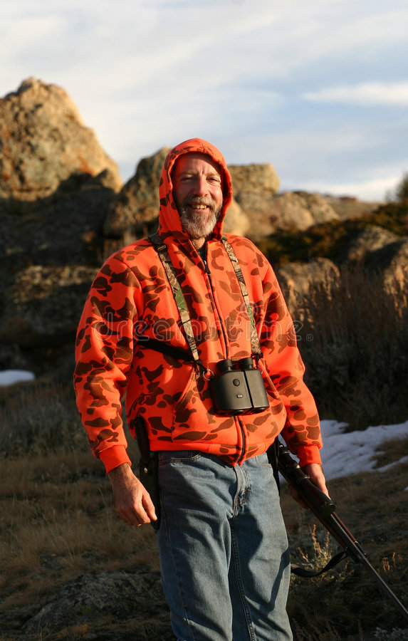 The Happy Hunter. A hunter decked out in blaze orange camouflage. Complete with rifle, binoculars, hunting knife and blue jeans. Evening setting sun, very cold stock images