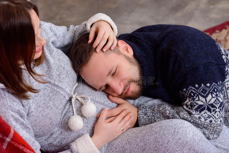 Happy husband listens to baby heartbeat lying on belly of his pregnant wife stock image