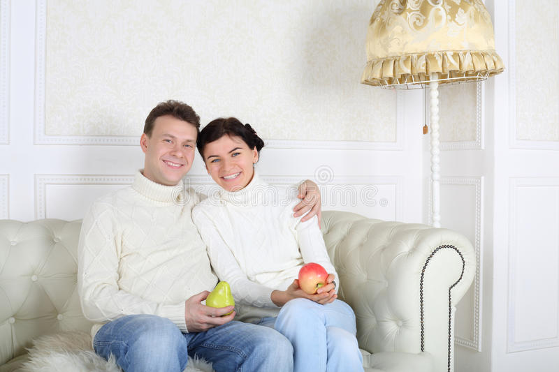 Happy husband and wife with fruit sit on white sofa. In white room at home stock photo