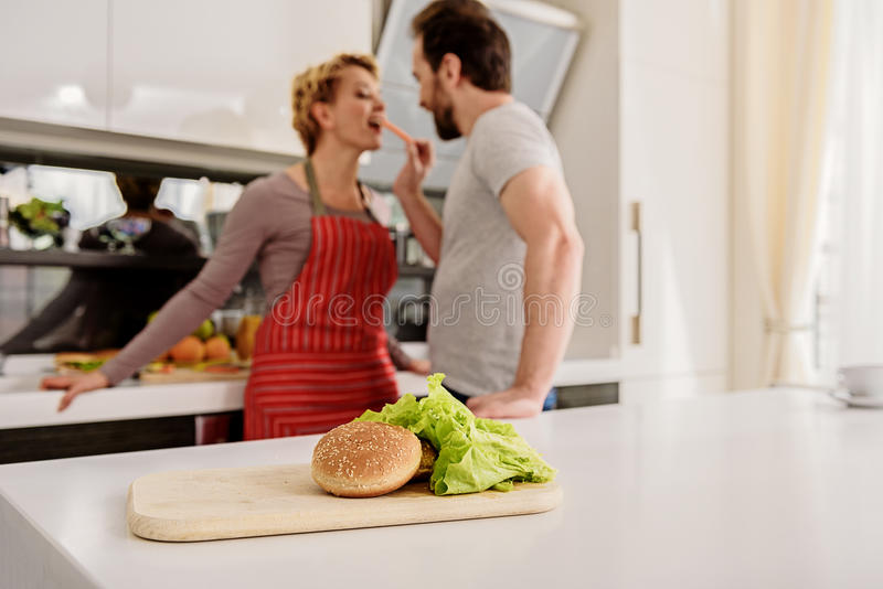Happy husband and wife having fun in kitchen stock photo