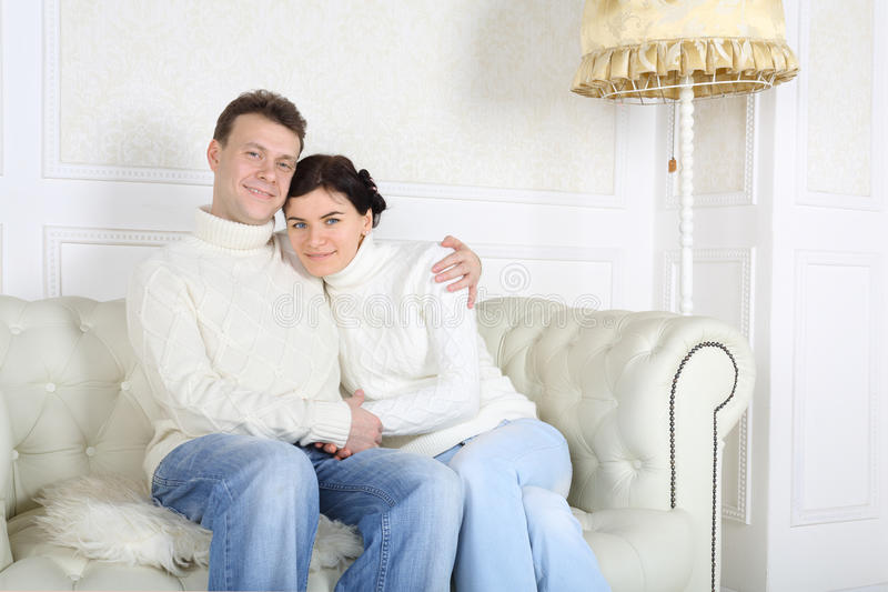 Happy husband and wife hug and look at camera. On white sofa at home royalty free stock image