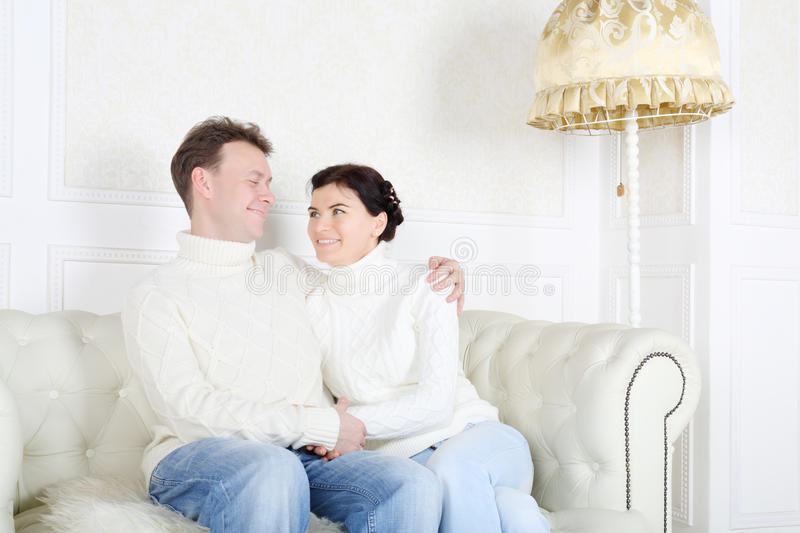 Happy husband and wife hug and look at each other. On white sofa at home stock images