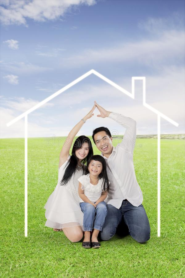 Happy family making hand made house on a meadow stock photography