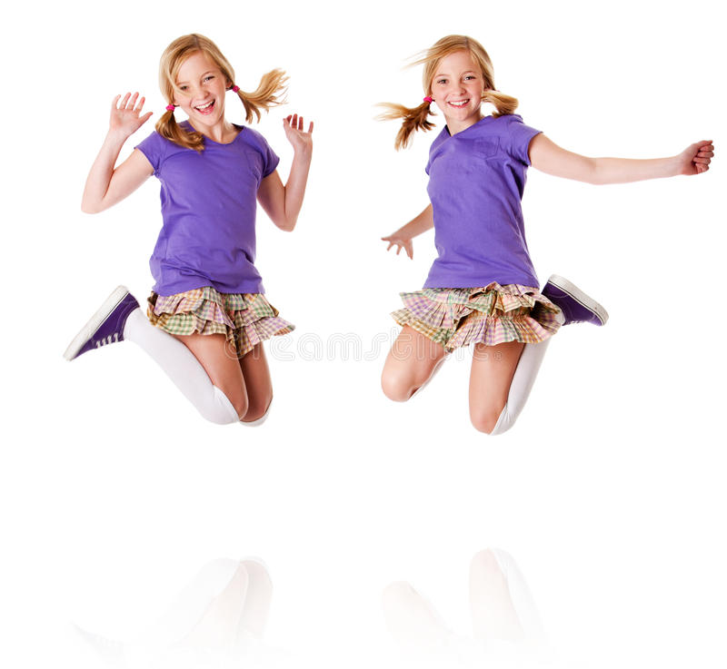 Happy identical twins jumping and laughing. Happy teenager girls identical twins jumping and laughing of happiness having fun, isolated royalty free stock image