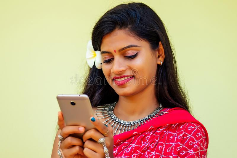 Happy india business lady white toothy smile in traditional Indian sari clothes red wedding dress holding a gadget in. Hand using the phone app in tropic island royalty free stock images