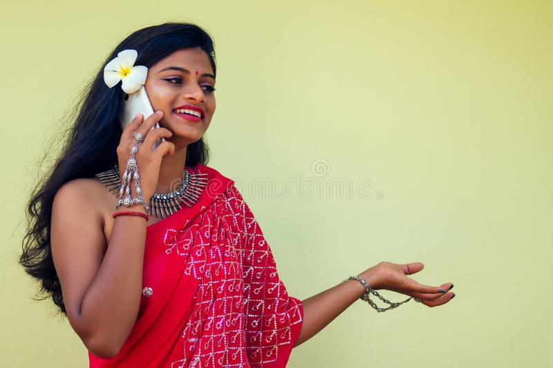 Happy india business lady white toothy smile in traditional Indian sari clothes red wedding dress holding a gadget in. Hand using the phone app in tropic island royalty free stock image
