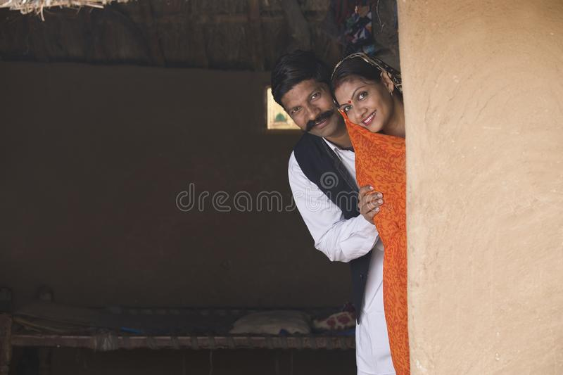 Happy indian couple peeking from rural house royalty free stock photos