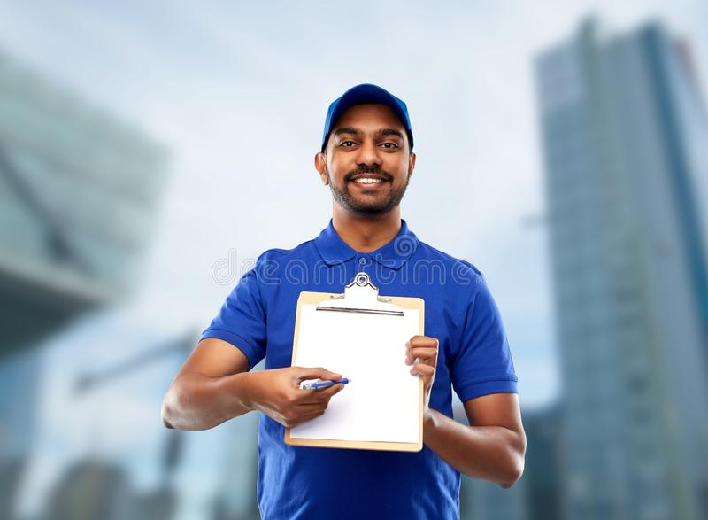 Happy indian delivery man with clipboard in blue. Mail service and shipment concept - happy indian delivery man with clipboard in blue uniform over tokyo city stock photos