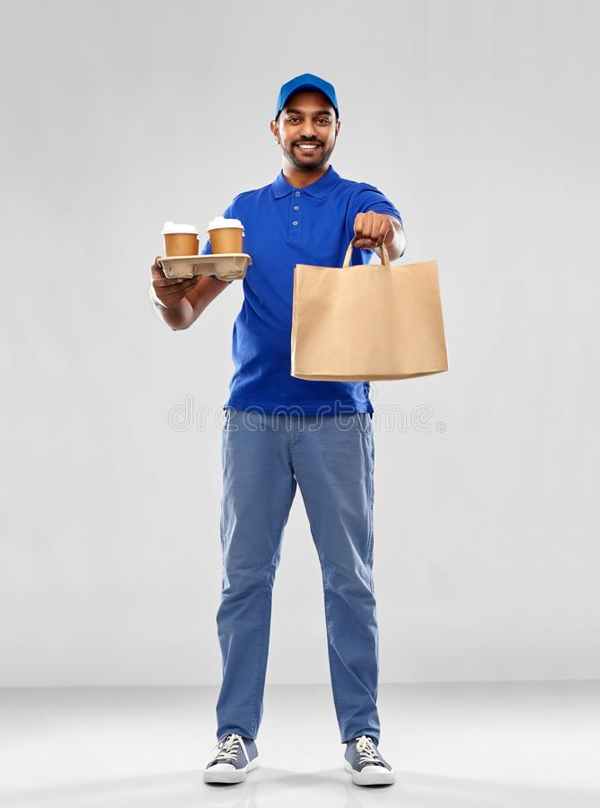 Happy indian delivery man with food and drinks. Service and people concept - happy indian delivery man with food in bag and drinks in blue uniform over grey stock photos