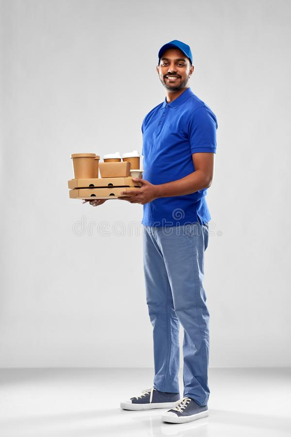Happy indian delivery man with food and drinks. Service and people concept - happy indian delivery man with food and drinks in blue uniform over grey background stock image