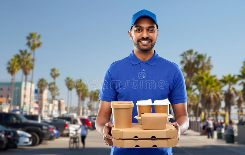 Happy indian delivery man with food and drinks. Takeaway service and people concept - happy indian delivery man with food and drinks in blue uniform over venice royalty free stock photos